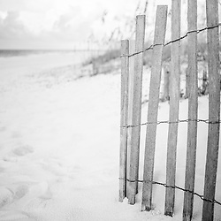 Beach fence in Pensacola Beach Florida black and white photo. Pensacola Beach is a coastal city in the Emerald Coast area of the Southeastern United States. Photo is vertical and high resolution. Copyright ⓒ 2018 Paul Velgos with All Rights Reserved.