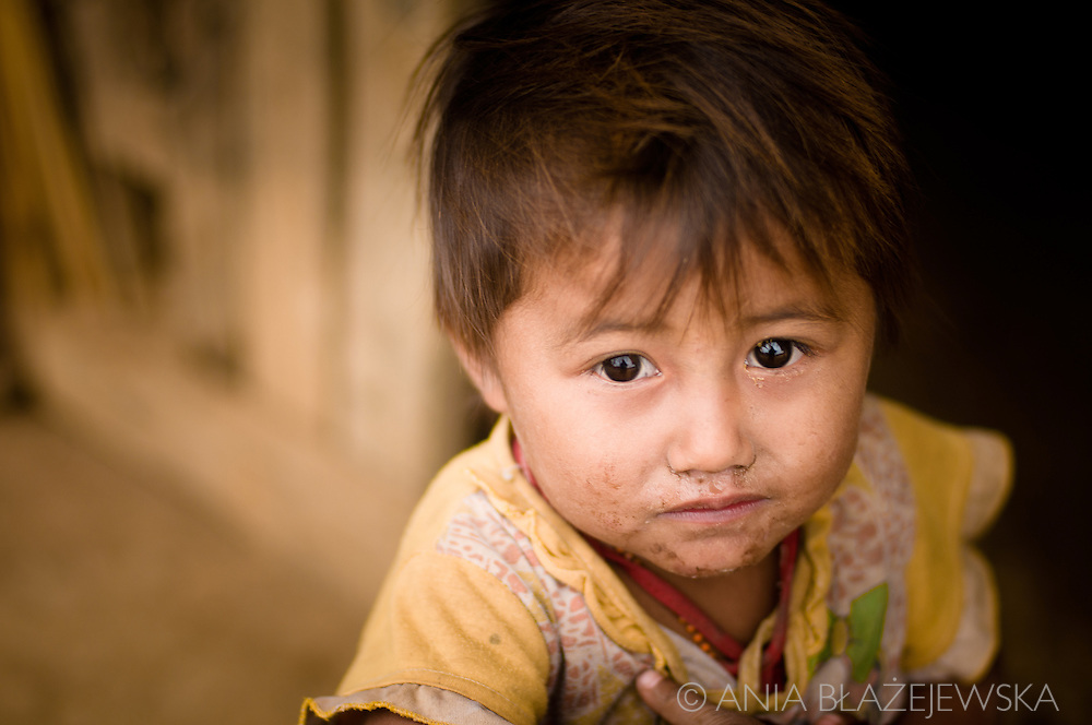 Laos, Ban Nam Pick. Little Khamu girl deep in her thoughts.