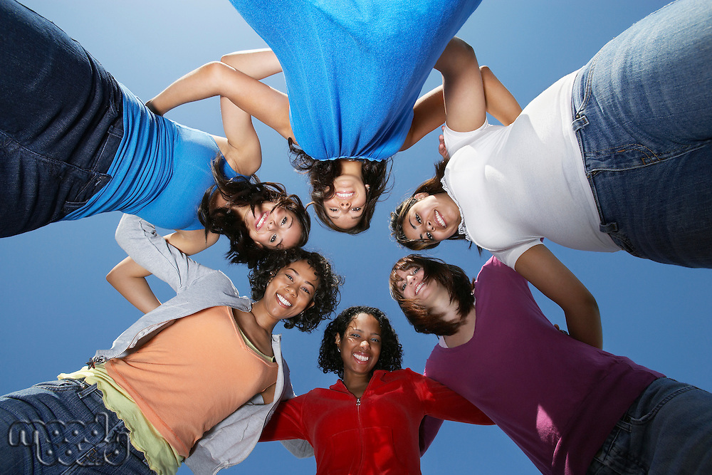 Young women standing in circle, view from below