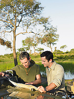 Two men reading map spread on bonnet of jeep