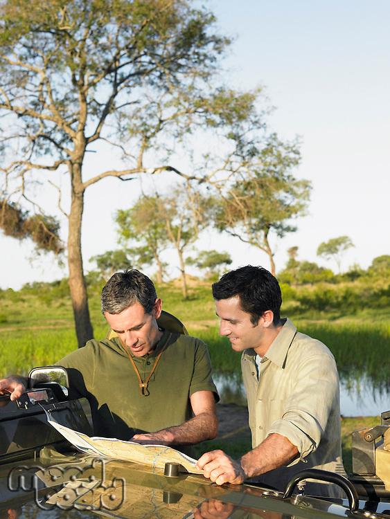 Two men reading map spread on bonnet of jeep