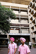 Två män i rosa turban och matchande skjorta utanför Punjab och Haryana High Court ritad av Le Corbusier och öppnades 1955, Chandigarh, Punjab, Indien.Two men in pink turbans och matching shirts outside the Punjab and Haryana High Court, architect Le Corbusier 1955, Chandigarh, Punjab, India.NOT FOR COMMERCIAL USE UNLESS PRIOR AGREED WITH PHOTOGRAPHER. (Contact Christina Sjogren at email address : cs@christinasjogren.com )