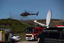 "© Licensed to London News Pictures . 28/06/2018 . Saddleworth , UK . A helicopter lands at Higher Swineshaw Reservoir . The army are being called in to support fire-fighters , who continue to work to contain large wildfires spreading across Saddleworth Moor and affecting people across Manchester and surrounding towns . Very high temperatures , winds and dry peat are hampering efforts to contain the fire , described as "" unprecedented "" by police and reported to be the largest in living memory . Photo credit: Joel Goodman/LNP"