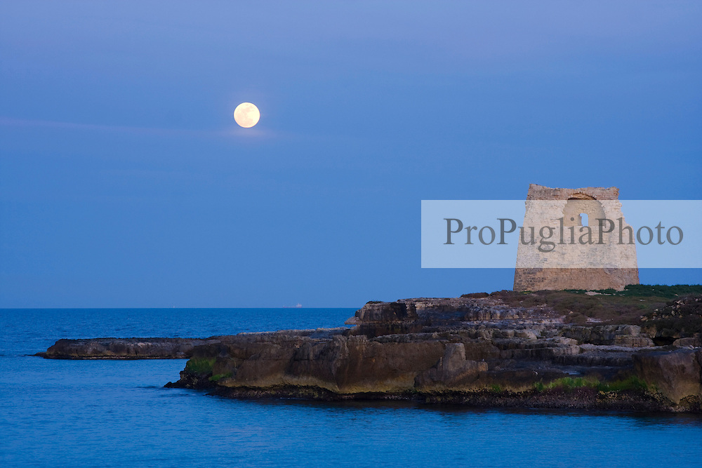 The old tower of Roca vecchia on the Adriatic sea with the full moon.