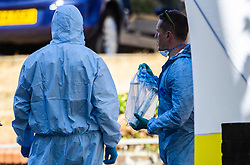 A forensics investigator holds and evidence container that appears to hold a long bladed knife as police investigate the killing of a man in his 20s at Cambridge Gardens in Norbiton, Kingston Upon Thames in West London. London, August 05 2018.