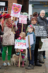 © Licensed to London News Pictures. 01/01/2019. Atherstone, North Warwickshire, UK. Anti Hunt protestors at the Atherstone Hunt meet in the Market Square, Atherstone Town Centre, Warwickshire. The traditional New Year's Day Hunt starts at Noon with speeches and a drink for the Huntsmen and women. Riders of all ages took part in the meet and there were protests from Anti Hunt protestors who had positioned themselves in the centre of the Market Square. The Hunt then formed up and rode from the town centre passing huge New Year's Day crowds that had come to see the spectacle. Photo credit: Dave Warren/LNP