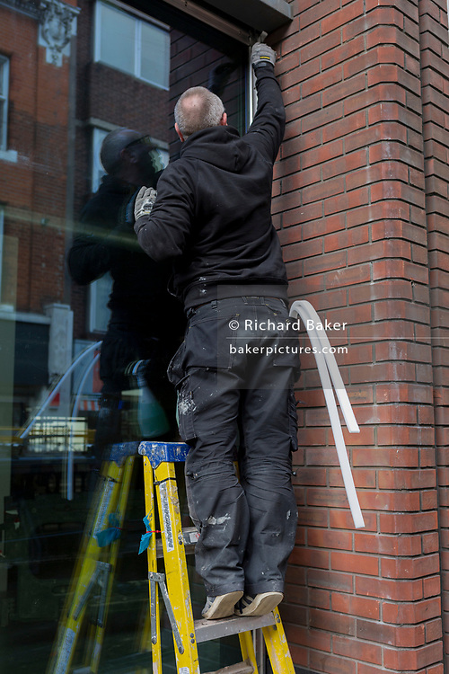 A workman up some stepladders reaches in the corner of a window recess in Soho, on 29th April 2019, in London, England.