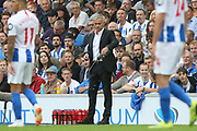 An unhappy Manchester United Manager Jose Mourinho pours drink on the floor during the Premier League match between Brighton and Hove Albion and Manchester United at the American Express Community Stadium, Brighton and Hove, England on 19 August 2018.