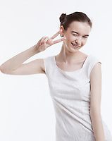 Portrait of young woman in dress gesturing peace sign over white background
