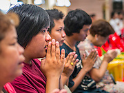 "12 OCTOBER 2012 - RAI KHRING, NAKHON PATHOM, THAILAND:   Thais pray during a Buddhist chanting and merit making service at Wat Rai Khring in Nakhon Pathom province. Wat Rai Khring was built in 1791, the Abbot at the time, Somdej Phra Phuttha Chan (Pook), named this temple after the district. When construction was completed, the Buddha image was brought from another temple and enshrined here. Later locals named the image ""Luang Pho Wat Rai Khing"". The Buddha image is of Chiang Saen style and is assumed to have been built by Lanna Thai and Lan Chang craftsmen.    PHOTO BY JACK KURTZ"