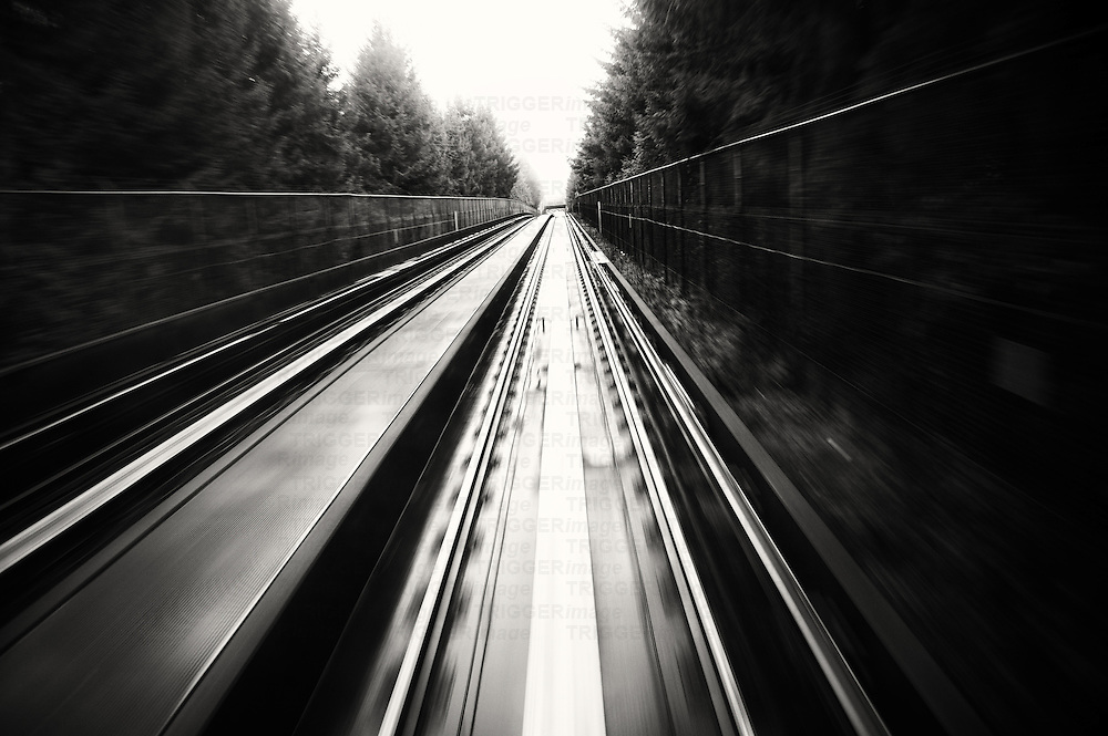 A view from a moving train, leaving a landscape and tracks in a vanishing point.