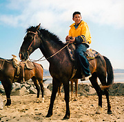 Teenage boy sat on a horse in the desert, USA