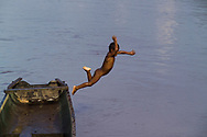 A young boy jumps off of a traditional Miskito dugout canoe into the Rio Coco in Krin Krin, Nicaragua. The river acts as a lifeline to villages along its banks. Indigenous residents use the river for bathing, washing, fishing and transportation, as there are no other ways to connect with the rest of Nicaragua from there without traveling the Rio Coco.