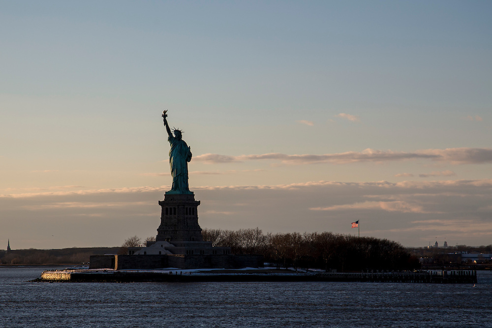 Silhouette of The Statue of Liberty on Liberty Island in New York Harbour, New York City, United States of America taken at dusk.  The flag of the United States of America flies in the background.  (photo by Andrew Aitchison / In pictures via Getty Images)