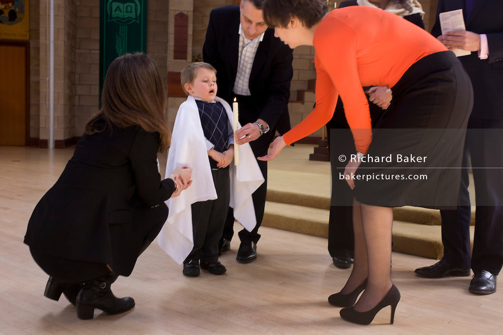 A 4 year-old's blows out a candle after his baptism ceremony in a local Catholic church