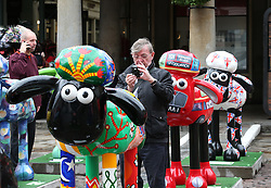© Licensed to London News Pictures. 24/09/2015. London, UK. People look at some of the 120 Shaun the Sheep sculptures placed in Covent Garden market ahead of their auction. The auction, on the 8th October 2015, will raise funds for the  Wallace & Gromit's Children's Charity supporting children's hospitals and hospices throughout the UK.  Photo credit: Peter Macdiarmid/LNP