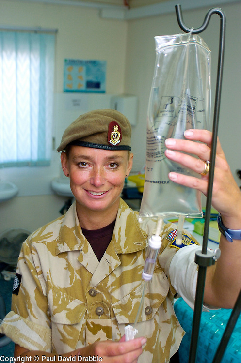 A British soldier, a female medic with the Muliti National Division in beret and desert camouflage uniform hangs a saline solution drip in the medical unit at Basra Air Station during Op Telic Iraq 2005