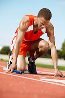 Runner Waiting in Starting Block holding Baton