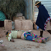 An injured villager, lies unconscious after fighting in the streets of Macha during the Tinku Festival. Macha, Bolivia, 4th May 2010, Photo Tim Clayton ..Each May, up to 3000 thousands indigenous Bolivian indians descend on the isolated mountainous village of Macha 75 miles north of Potosi in the Bolivian Andes. The 600 year old pre-hispanic Bolivia Festival of Tinku sees villagers from all over the region march into town to be pitted against each other in a toe to toe fist to fist combat.. They dance and sing in traditional costume and drink 96% proof alcohol along with chicha, a fermented beverage made from corn. Townspeople and sometimes the police oversee proceedings who often use tear gas to try and control the villages, whipped into a fighting frenzy by the dancing and alcohol, but as the fiesta goes on things often escalate beyond their control, with pitched battles between rival villages break out,  The blood spilt is an offering to the earth goddess - Pachamama - to ensure a good harvest for the coming year. Over the years dozens have died, yet the rite continues.