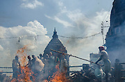 The ghats worker use bamboo poles to move incinerated corpse in the fire.<br />