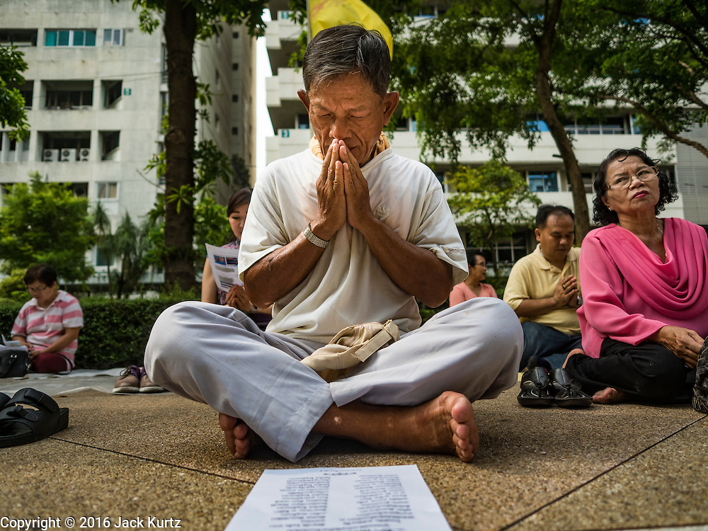 13 OCTOBER 2016 - BANGKOK, THAILAND:  A man prays for Bhumibol Adulyadej, the King of Thailand, at Siriraj Hospital Thursday morning before the King's death was announced. Thousands of people came to the hospital to pray for the beloved monarch. Bhumibol Adulyadej, the King of Thailand, died at Siriraj Hospital in Bangkok Wednesday, October 13, 2016. Bhumibol Adulyadej, 5 December 1927 – 13 October 2016, was the ninth monarch of Thailand from the Chakri Dynasty and is known as Rama IX. He became King on June 9, 1946 and served as King of Thailand for 70 years, 126 days. He was, at the time of his death, the world's longest-serving head of state and the longest-reigning monarch in Thai history.      PHOTO BY JACK KURTZ
