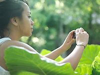 Young woman taking photograph of leaf side view