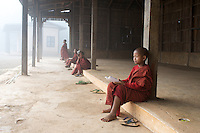 Hti Tain Monastery sits along a trek between Kalaw and Inle Lake in Burma.  Here novice monks gather early on a foggy morning for studies.