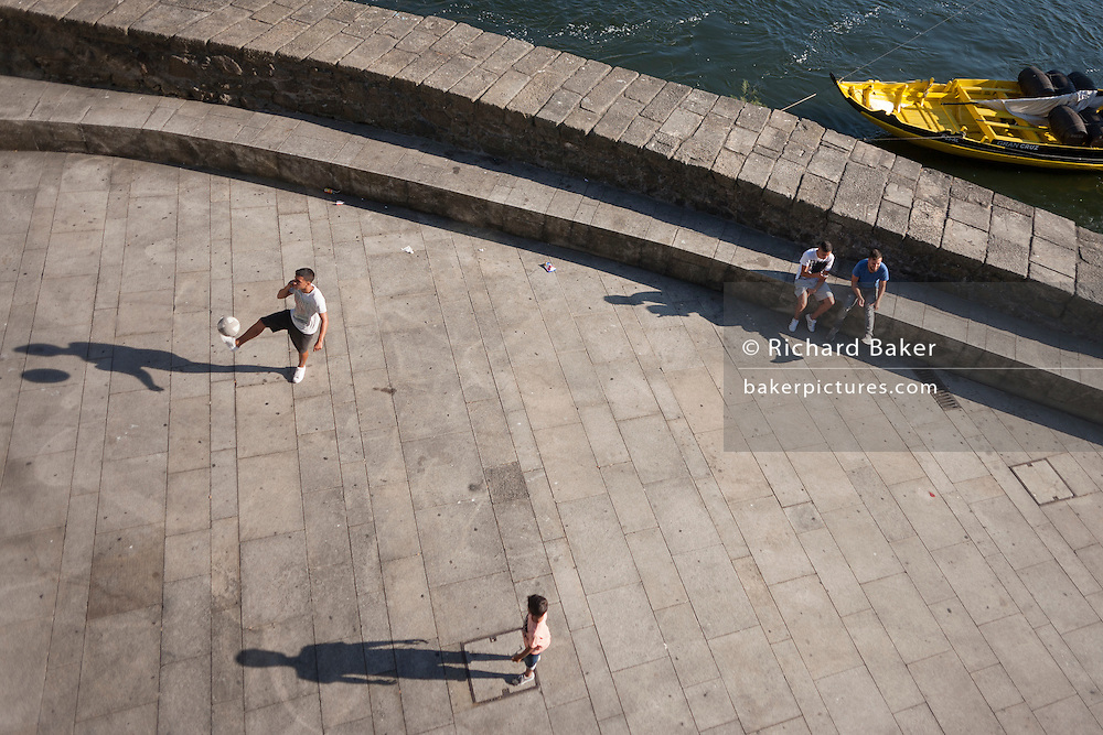 Aerial view of young men during a kickabout on the riverfront of the Douro in Porto, Portugal.