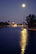 boats in canal & in marina, full moon reflected in water; Punta Gorda FL; Florida