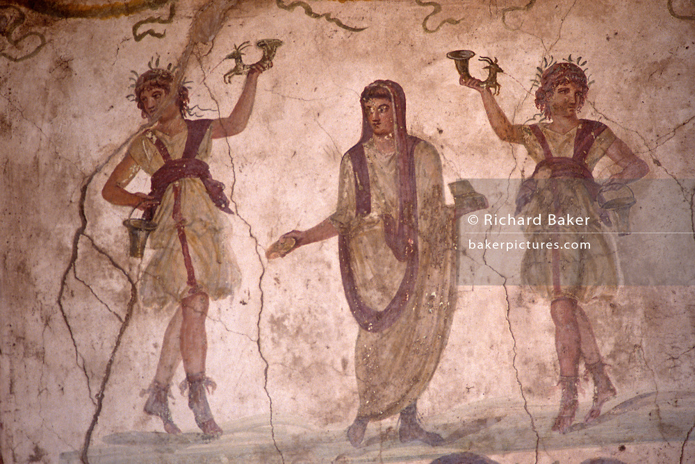 In the Villa of the Vettii in Pompeii we see a fresco in the lararium where a shrine to Roman guardian spirits of the household was situated. Family members performed daily rituals here to guarantee their protection by these domestic spirits. The first two characters are the deeply venerated 'lares' (presumed sons of Mercury and Lara) depicted as two young men in dancing postures, holding drinking horns that guaranteed prosperity. In the centre is the 'genius'. She is another guardian and fertility spirit ensuring the family line (gens) would continue and she wears the 'toga praetexta', bordered in purple, the garment of high-ranking Roman magistrates. Painted before the catastrophic eruption of Versuvius in AD79, these frescoes have been uncovered from metre-layers of volcanic ash and pumice but are now fading from moisture and cracked plaster...