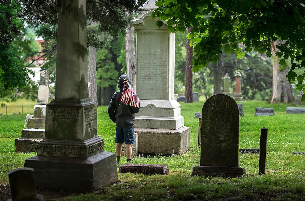 Blake Harris with Boy Scout Troop 303 paused during his troop's flag marking to read the headstone inscription of a burial monument Saturday morning in Union Cemetery in Kansas City, Mo.