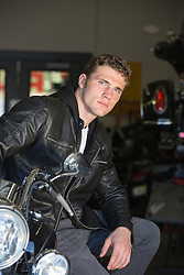 rugged man sitting on a Harley Davidson Motorcycle in a garage