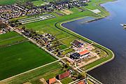 Nederland, Groningen, Oldambt, 01-05-2013; boerderijen in Oostwold, aan de oevers van het Oldambtmeer, onderdeel van Blauwestad. Het meer dienst voor recreatie en waterberging.<br /> Het project Blauwe Stad was oorspronkelijk bedoeld om de economisch achtergebleven regio van Noordoost Groningen een impuls te geven. De economische en huizen crisis gooit echter roet in het eten.<br /> Old farms on the edge of the new recreational Oldambt lake, part of Blauwestad (Blue City), the newly constructed residential area. The Oldambt lake also serves as water storage. The Blue City project is meant to give a boost to the  economically backward region of northeast Groningen, but the financial crisis has slowed down real estate developments.<br /> luchtfoto (toeslag); aerial photo (additional fee required);<br /> foto Siebe Swart / photo Siebe Swart1