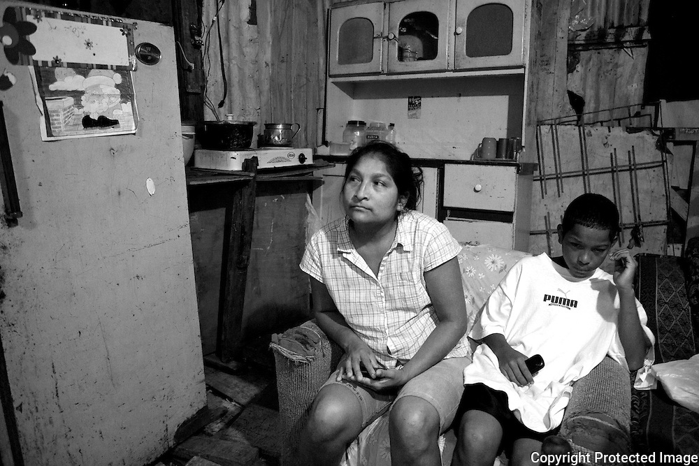 Kevin, 12, sits in a sofa chair with his mother while discussing the possibility of placing him in a state home with other children who are also unable to live at home. Kevin thinks he wants to go but is still unsure. There are many consequences to leaving home to becpme a warden of the state, but remaining in the slum with no father and a mother who is not around often is not a good option either.