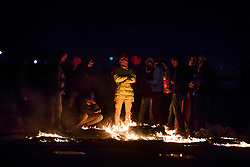 © Licensed to London News Pictures. 23/10/2016. Calais, France. A group of migrants stand over burning remains as they clash with French police on the eve of the demolition of the camp. French authorities have given an eviction order to thousands of refugees and migrants living at the makeshift living area of the French coast. Photo credit: Ben Cawthra/LNP