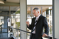 Businessman leaning on railing using mobile phone.