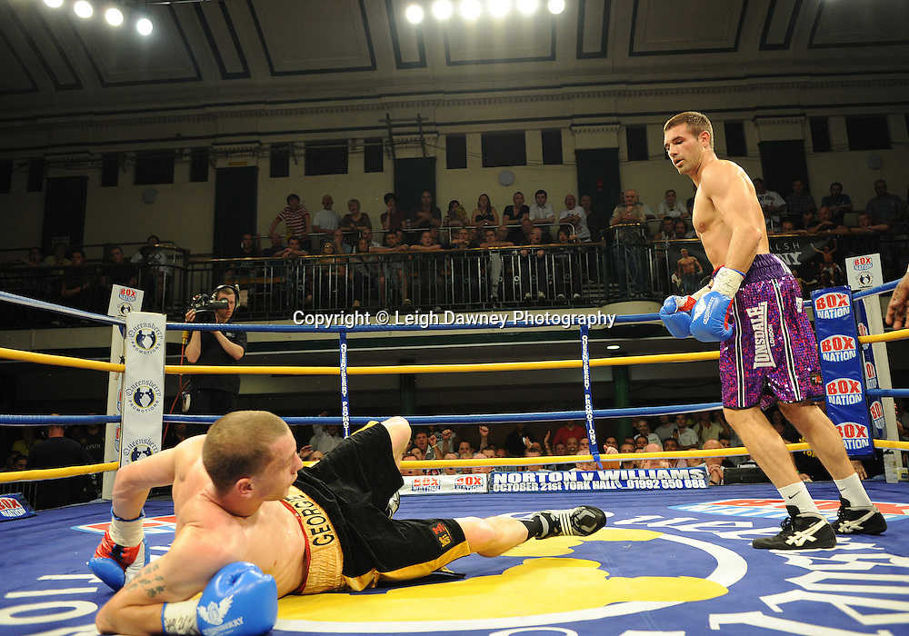 Steve O'Meara (purple shorts) knocks down Ryan Toms at The Southern Area Light-Middleweight Championship at York Hall, Bethnal Green, London on Friday 30th September 2011. Box Nation.tv's debut live TV Channel 456 on Sky. Photo credit: © Leigh Dawney. Queensberry Promotions.