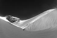 Two ski tourers are climbing up to mount Glatten, Muotathal, Schwyz, Switzerland