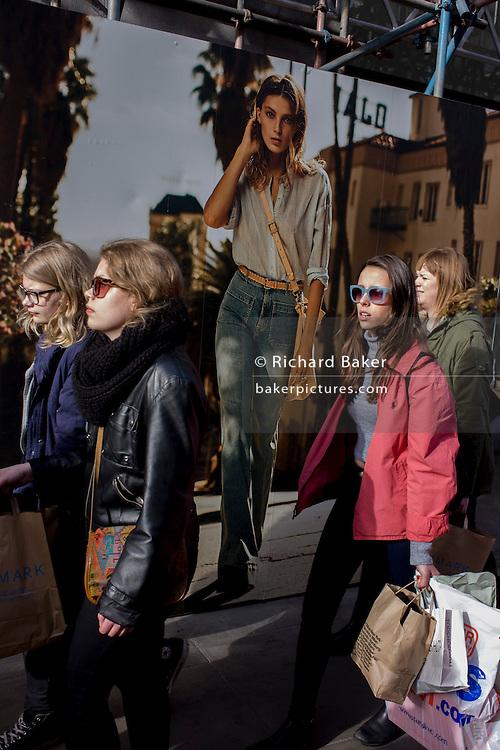 Women street shoppers in cenral London walk past an H&M fashion poster