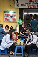 Locals sitting on low plastic seats eating street food in the Old Quarter, Hanoi, Vietnam, Southeast Asia