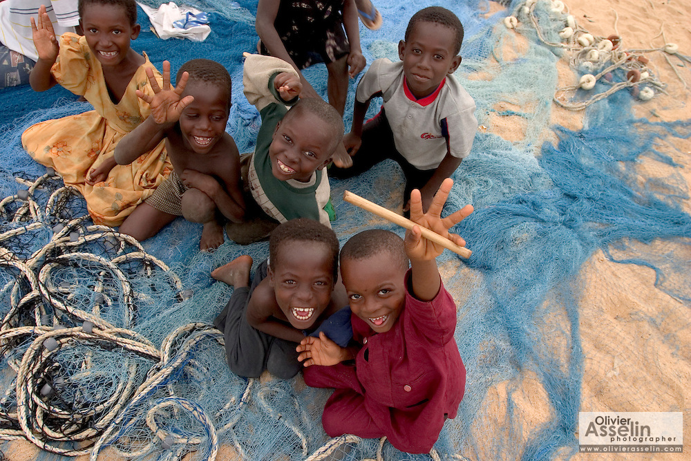 Children playing on fishing nets on the beach at Aflao, Volta region, Eastern Ghana.