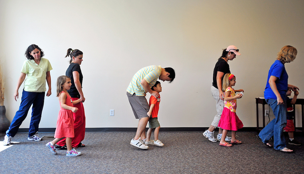 Jae Park, center, talks with his son, Gyumyn Park as they take an imaginary bus ride to Old MacDonald's farm during a preview Musikgarten early childhood music education class at Chik Music on Thursday, Aug. 19, 2010 in Athens, Ga. .