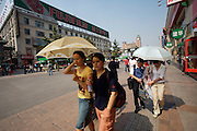 Wangfujing Dajie shopping street and pedestrian zone. Shoppers with umbrellas.