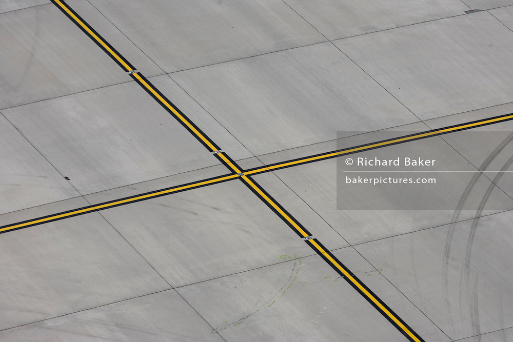 High aerial view (from control tower) of Heathrow airport diagonal aviation markings on concrete landscape.