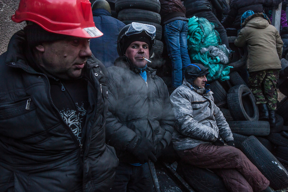 KIEV, UKRAINE - JANUARY 25: Anti-government protesters rest against a barricade made of tires on Hrushevskoho Street near Dynamo stadium on January 25, 2014 in Kiev, Ukraine. After two months of primarily peaceful anti-government protests in the city center, new laws meant to end the protest movement have sparked violent clashes in recent days. (Photo by Brendan Hoffman/Getty Images) *** Local Caption ***