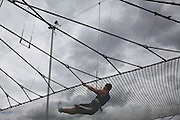 Student Danial Adkison dismounts into the net at Trapeze School New York during the June 4th morning class. The two hour beginner session taught the nine students in attendance the basics of flying trapeze -- including knee hangs and backwards somersaults -- in their facility on the roof of Pier 40...CREDIT: Daniella Zalcman for The Wall Street Journal.SLUG: NYMETROMONEY_Trapeze