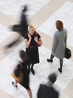 Business woman using mobile phone standing amongst people walking elevated view long exposure