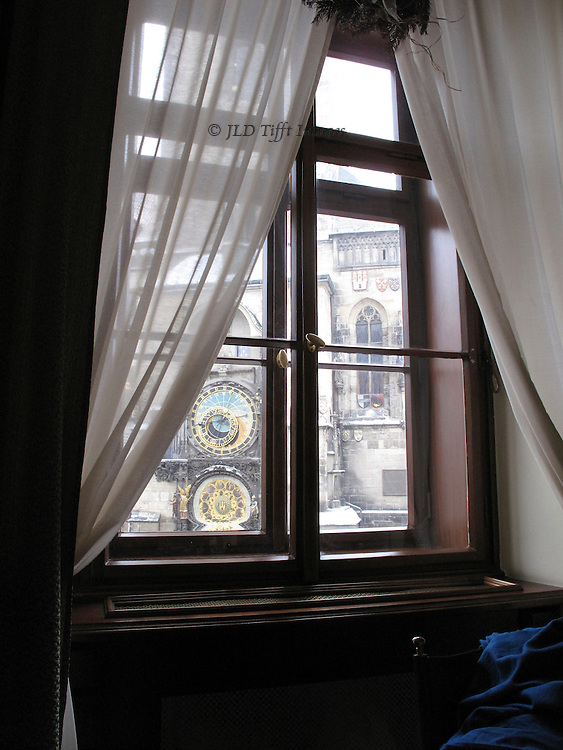 Soft white curtains drawn back from the window overlooking the Old Town Square in Prague, giving a glimpse of the famous astronomical clock.  A blue coat is thrown over a chair in front of the window, which is in a restaurant upstairs in a bank across the street from the clock.  Feeling of being inside and looking out.