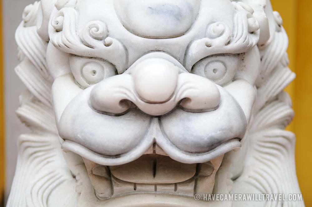 Close-up front on view of an ornately carved white marble lions guard the entrance to a gate at the One Pillar Pagoda next to the Ho Chi Minh Museum in the Da Binh district of Hanoi, Vietnam.