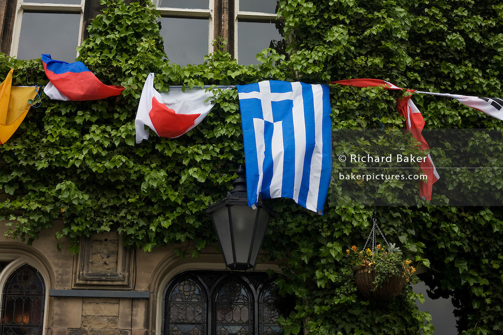The Greek national flag hangs awkwardly with other nations outside a Buxton pub.